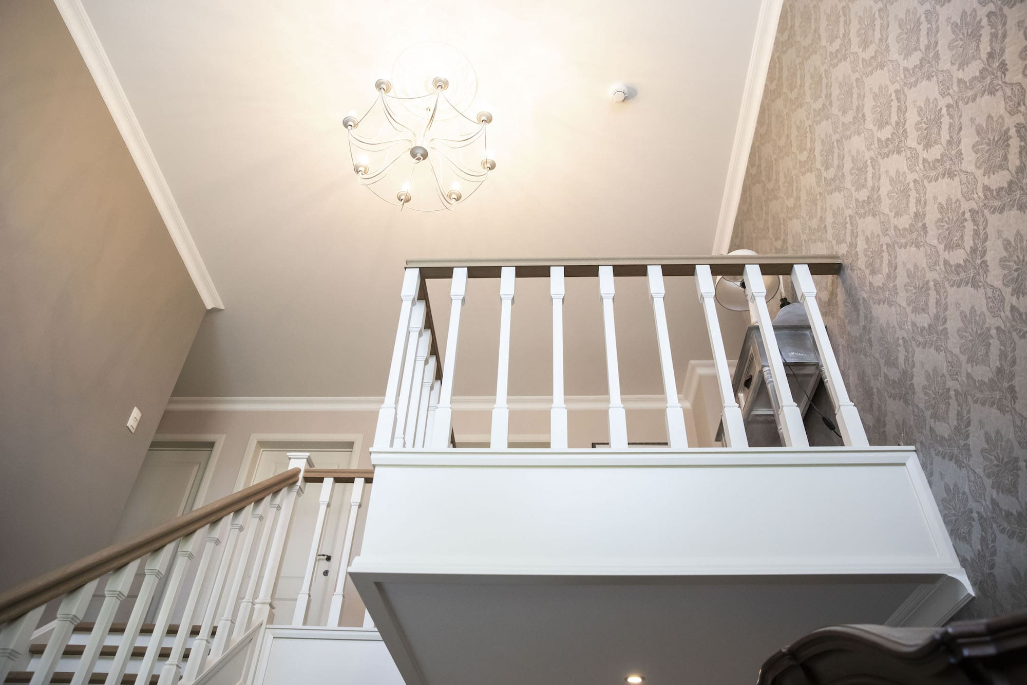 Traditionele gesloten trap met leuning model Victoria. Tredes en handgreep in Franse eik, overige delen zijn gelakt